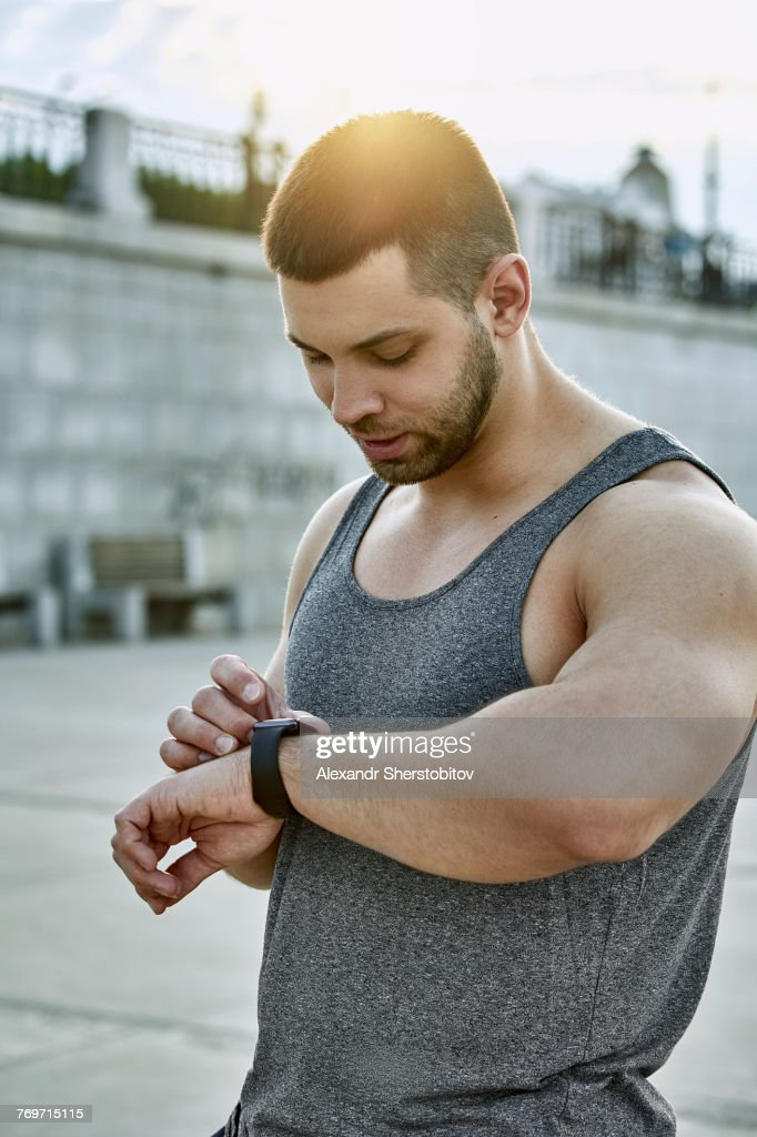 Male athlete using smart watch while standing at footpath : Stock Photo