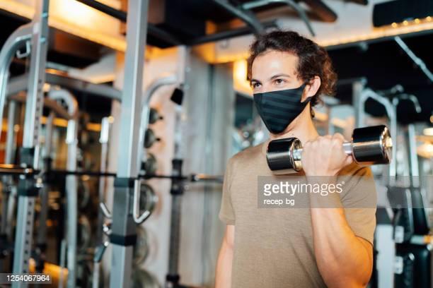 mannelijke atleet die beschermend gezichtsmasker en opleiding met halter in gymnastiek draagt - sportsperson stockfoto's en -beelden