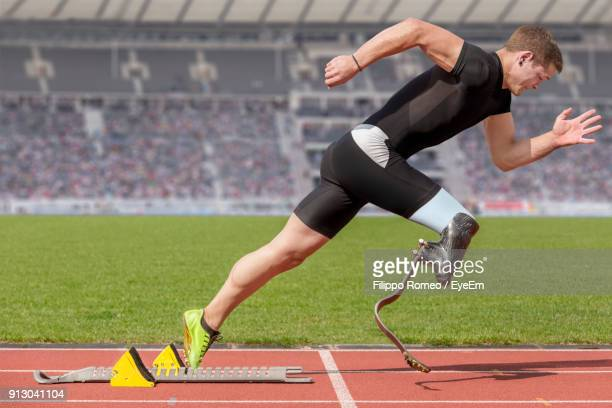 male athlete with amputated leg on running on track - assistive technology stock photos and pictures