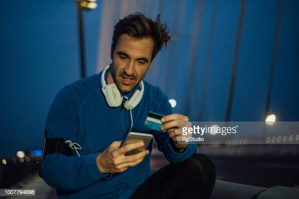 male athlete with headphones shopping online after outdoor night run - charging sports stock pictures, royalty-free photos & images