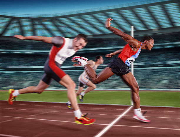 Male athletes at finishing line, winner crossing line (Composite)