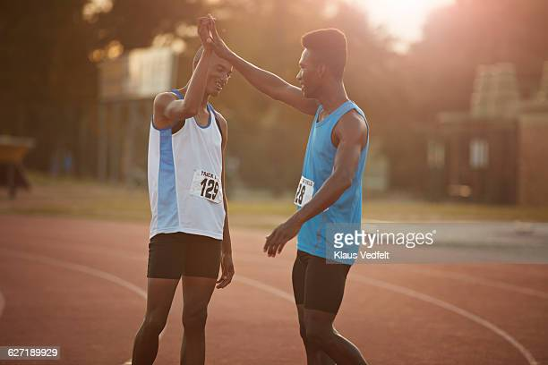 Male athletes giving high five at stadium