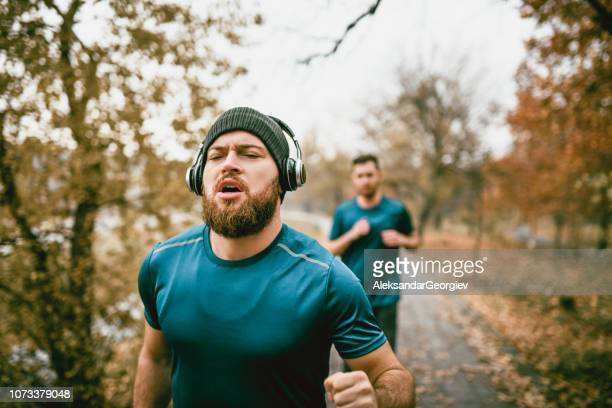 Male Athletes Jogging In a Public Park