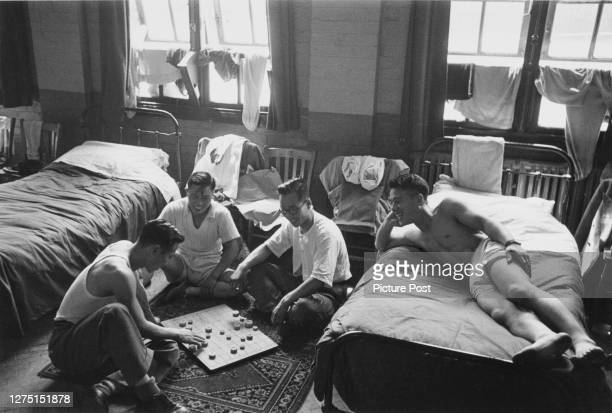 Male athletes of the Korean team relaxing with a board game in their accommodation at an RAF camp in Uxbridge, London, England, July 1948. Dubbed the...