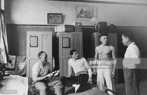 Male athletes of the Korean team talking with their hostel manager, in the background are three wardrobes and two flags , in their accommodation at...