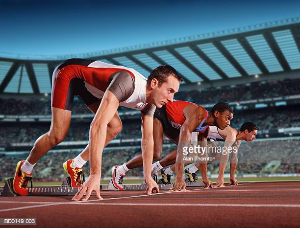 male athletes poised on starting blocks (digital composite) - track and field stadium stock pictures, royalty-free photos & images