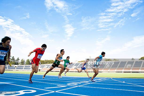 male athletes running to the finish line - forward athlete stock pictures, royalty-free photos & images