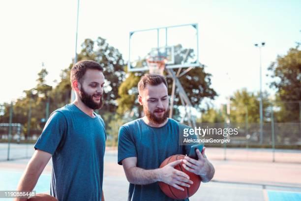 männliche athleten versuchen, basketball bewegt von smartphone-video zu replizieren - sporting term stock-fotos und bilder
