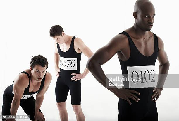 Male athletes with hands on hips, studio shot