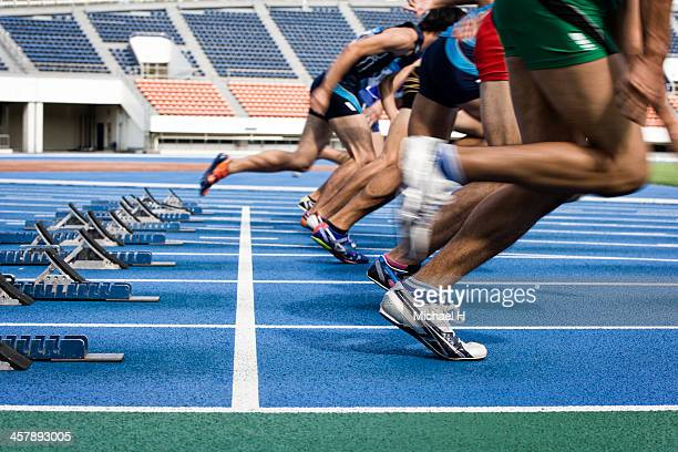 male athltes starting from blocks on track