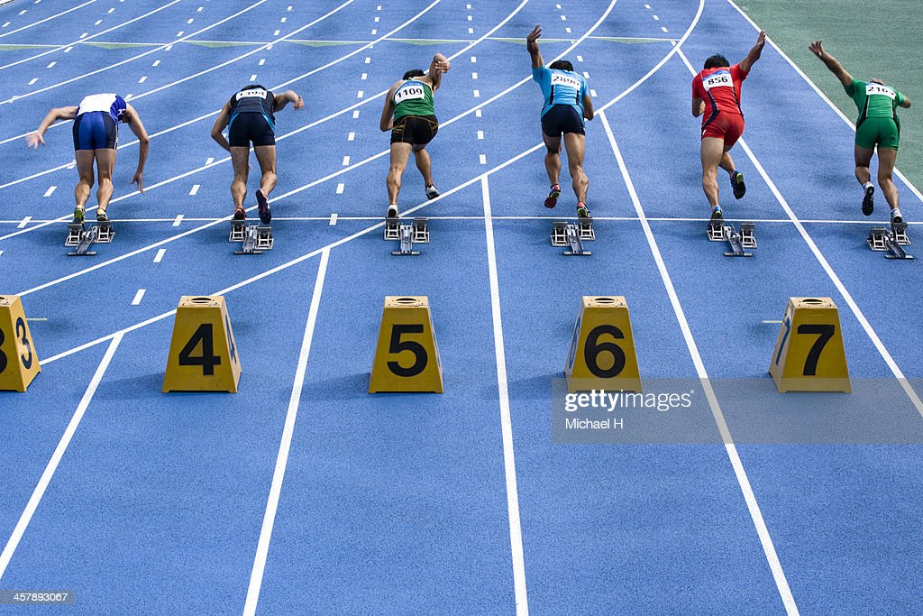 male athltes starting from blocks on track : Stock Photo