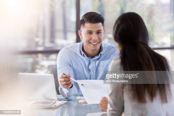 male attorney gestures at contract in front of client - social grace stock pictures, royalty-free photos & images