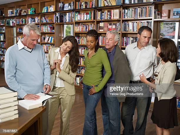 male author signing books for customers in bookstore - lançamento de livro evento publicitário - fotografias e filmes do acervo