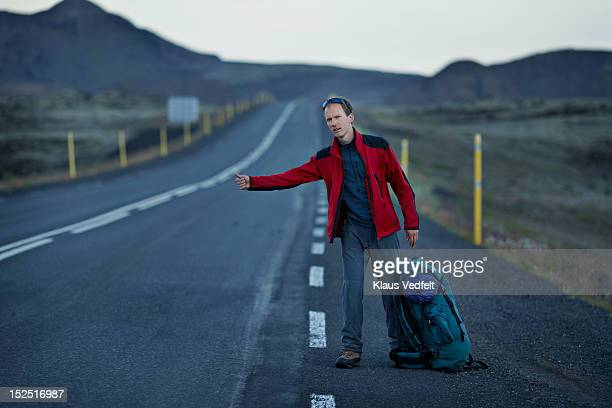 Male backpacker hitch hiking on long mountin road