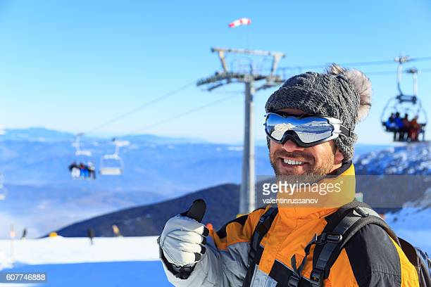 Male backpacker standing in front of a chair lifts