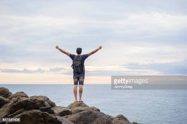 Male backpacker standing on rocks with arms outstretched
