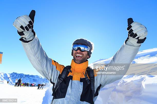 Male backpacker with thumbs up on top snow mountain