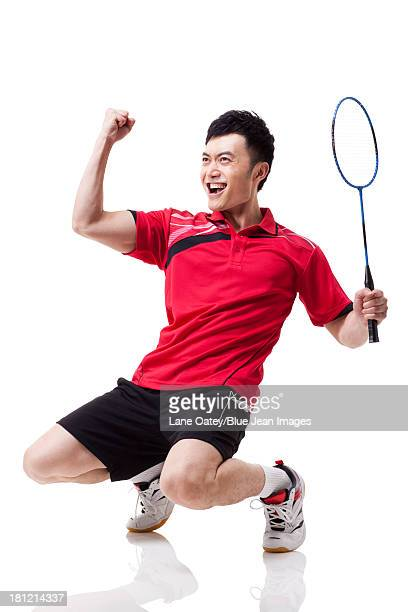 male badminton player celebrating with excitement - badminton sport stock pictures, royalty-free photos & images