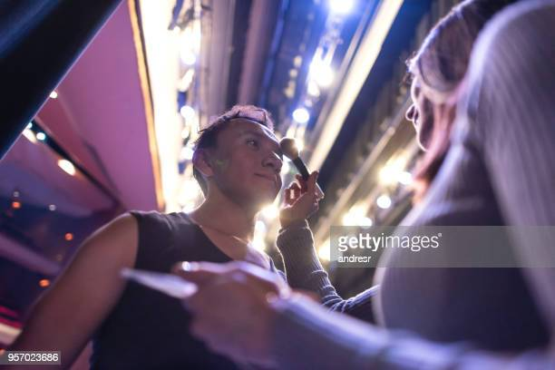 male ballet dancer getting a retouch on his make up from a professional make up artist - dietro le quinte palcoscenico foto e immagini stock