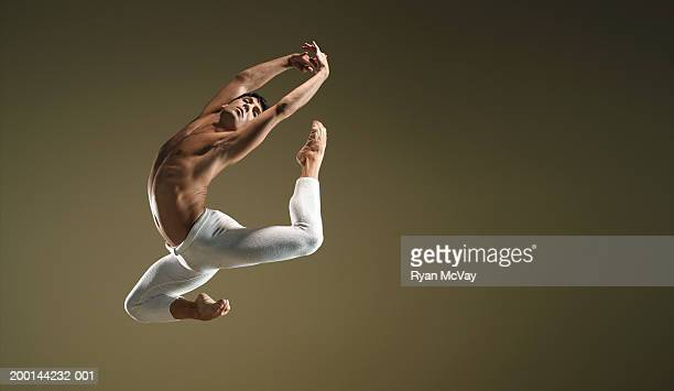 Male ballet dancer in mid air pose