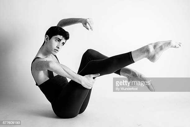 Male ballet dancer in tights with his legs up