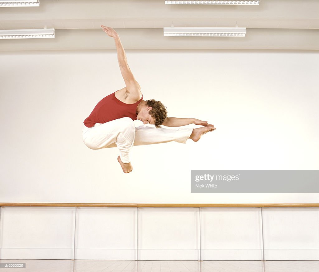 Male Ballet Dancer Jumping in Mid Air With One Arm Out And His Head Touching His Leg : Stock Photo
