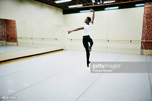 Male ballet dancer leaping in air during practice