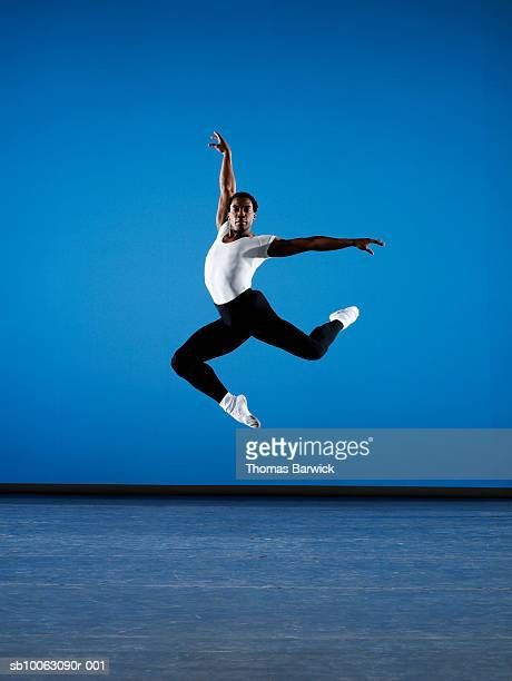 Male ballet dancer leaping on stage