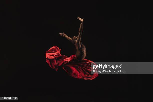 male ballet dancer performing against black background - black skirt stock pictures, royalty-free photos & images