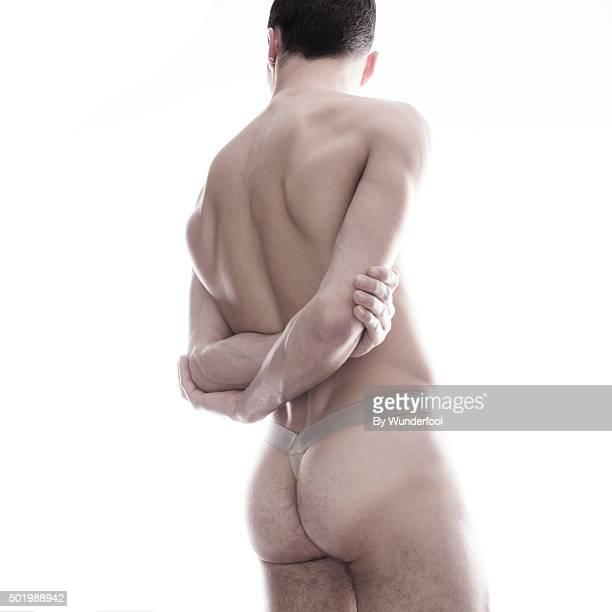 Male ballet dancer posing against backlight