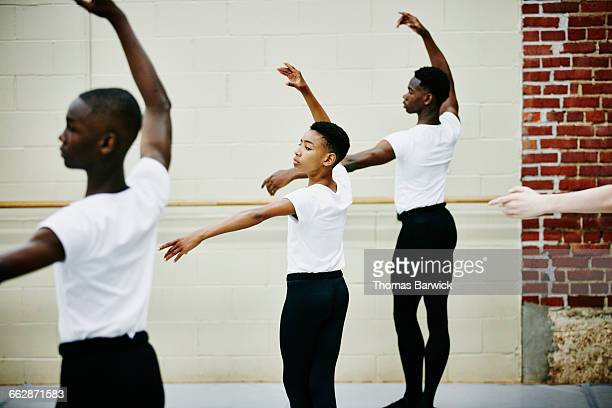 Male ballet dancer practicing with classmates