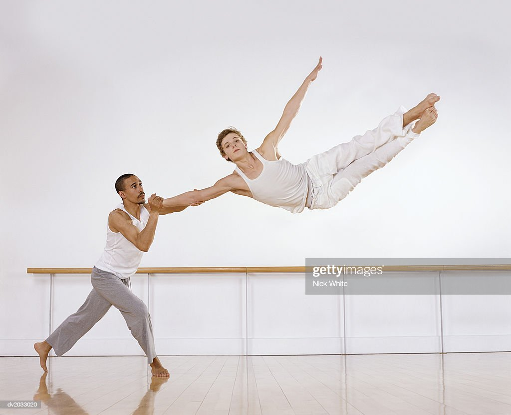 Male Ballet Dancer Supporting a Female Ballerina Jumping Mid Air : Stock Photo