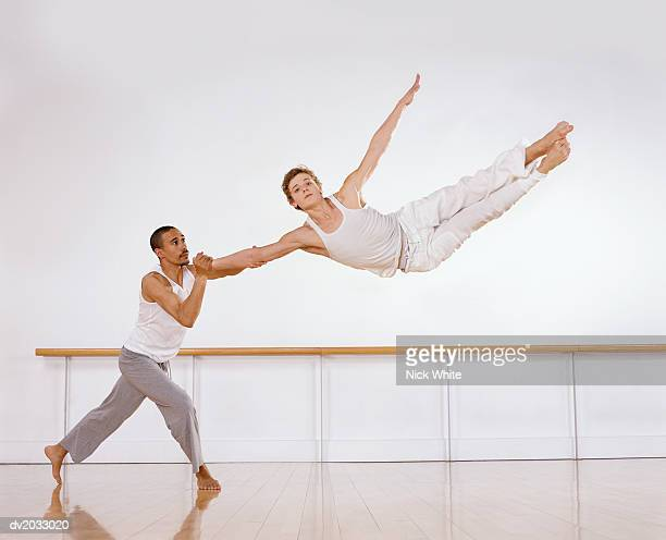 Male Ballet Dancer Supporting a Female Ballerina Jumping Mid Air