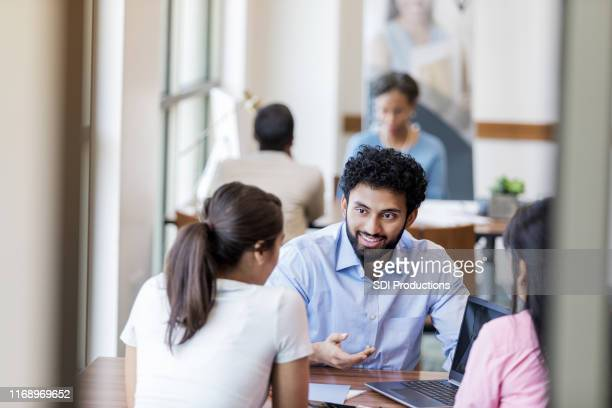 Male bank employee discusses new account with customers
