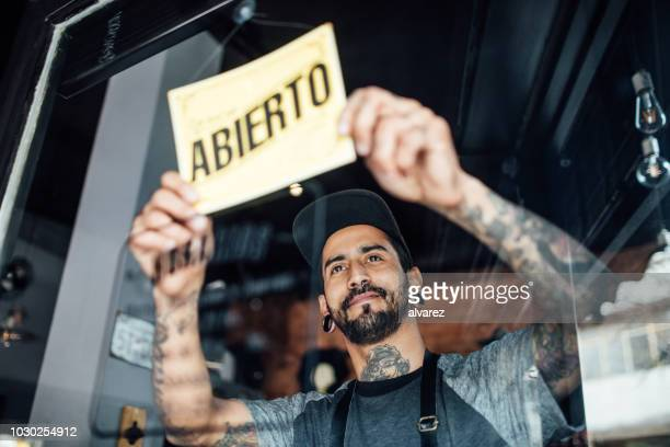 male barber hanging an open sign on glass door - opening event stock pictures, royalty-free photos & images