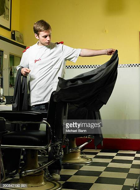 Male barber holding aprons, low angle view