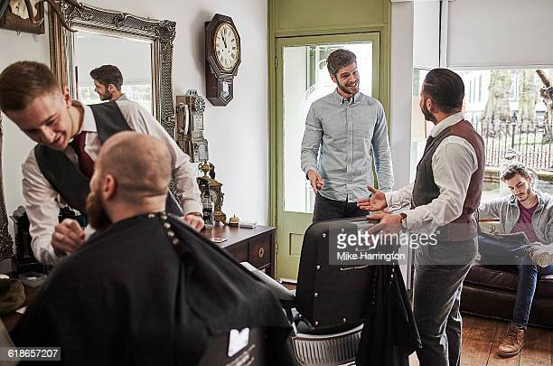 Male barber inviting customer to take a seat