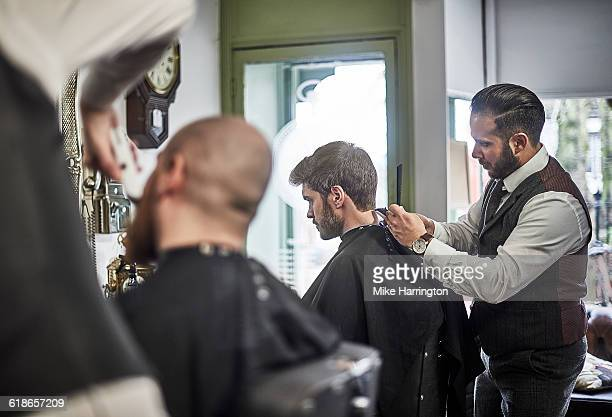 Male barber perfecting hair cut