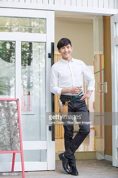Male barber standing in doorway of barber shop