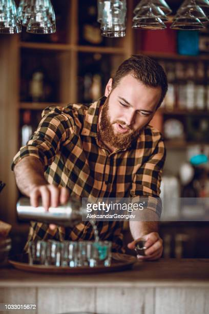 male barista makes cocktail shots during party - scotch whiskey stock pictures, royalty-free photos & images