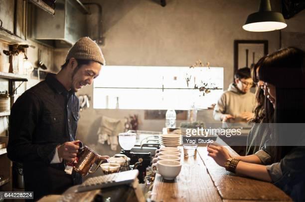 男性のバリスタのコーヒー ショップでコーヒーを作る