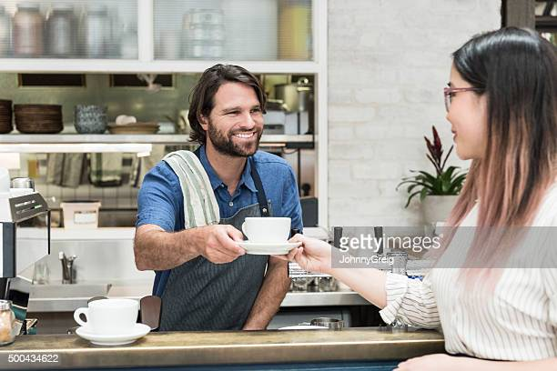 Male barista serving fresh coffee to female customer