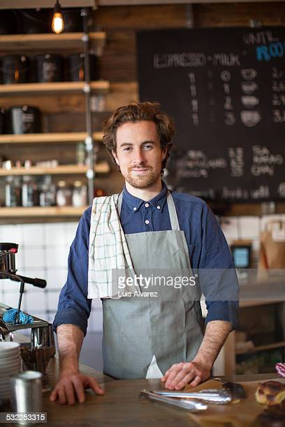 Male barista standing at cafe counter