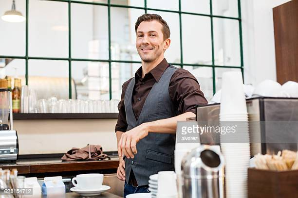 Male barista standing cafe counter