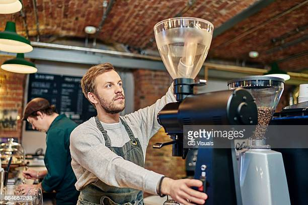 Male barista using coffee machine at coffee shop kitchen counter
