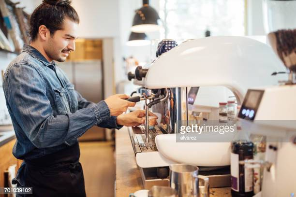 Male barista using coffee maker in cafe