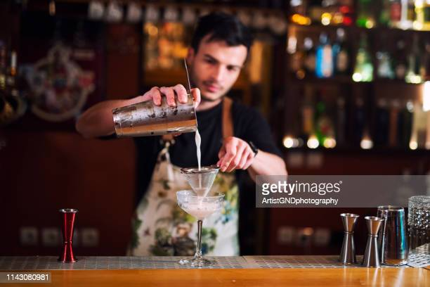 male bartender pouring alcohol in glass, a young bartender making luxury cocktail. - bartender stock pictures, royalty-free photos & images