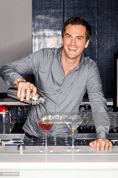 Male Bartender Pouring Cocktail In Martini Glasses At Counter