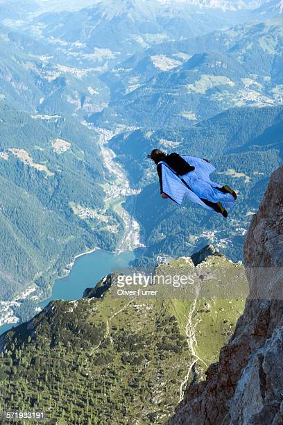Male BASE jumper wingsuit flying over valley, Dolomites, Italy