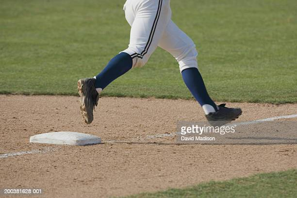 Male baseball player running across third base, low section, side view